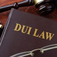 DUI Law title on a book with glasses, gavel and pen on desk