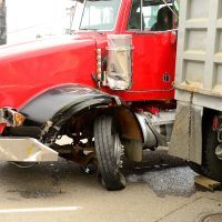 aftermath of a large red truck jackknifing