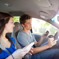 Guy and girl on their phones while driving
