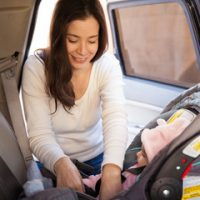 mom strapping kid in car seat