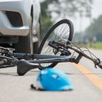 aftermath of car accident with cyclist with helmet and bicycle in view