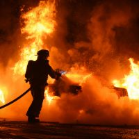 Fireman putting out fire from the remains of a car crash