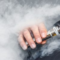 A man smokes an electronic cigarette on a gray background, blowing a stream of smoke. Copy space.