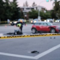 Accident of motorcycle and car at crossroad, blurred