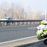 Artificial white roses flowers on the site of a car crash traffic accident on the bridge safety metal fence with a fatal outcome with vehicle movement