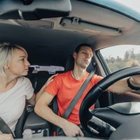 Wife wakes up tired husband, falling asleep at wheel of car. Dangerous sleep while driving. Accident on road, driver fainting