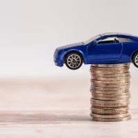 Car on stack of coins. Car loan, Finance, saving money, insurance and leasing time concepts.